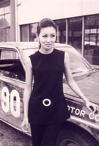 年代を感じる車の前に手を置いて立つ浅丘ルリ子